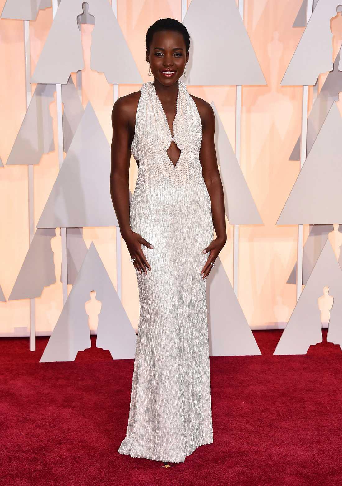 """Lupita Nyong'o 2015 """"Ibland är enklast helt enkelt bäst. Den här klänningen från Prada är motsatsen till Amy Adams fjäderklänning men precis lika majestätisk. När Lupita höll sitt tacktal och när inget öga var torrt kunde man bara sitta tillbaka, beundra och inse att ibland står alla stjärnor bara rätt på himlen."""""""