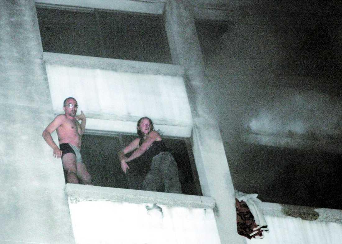 BÖRJADE VID MIDNATT Hotellgästerna försöker fly undan lågorna och den kraftiga röken på hotell Mandarin i Bangkok. Flera av dem fick tas ut genom fönstren med hjälp av brandkårens stegbilar.