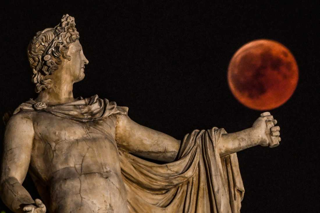 Grekiska guden Apollo beundrar blodmånen i centrala Aten.