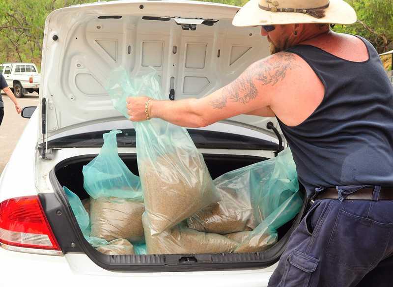 Bunkrar sandsäckar En boende i Townsville förbereder sig inför cyklonen Yasi genom att packa bagaget fullt med sandsäckar. Delar av Queensland hotas av översvämningar och nu bygger man vallar med hjälp av sandsäckar för att hålla vattenmassorna borta från husen.
