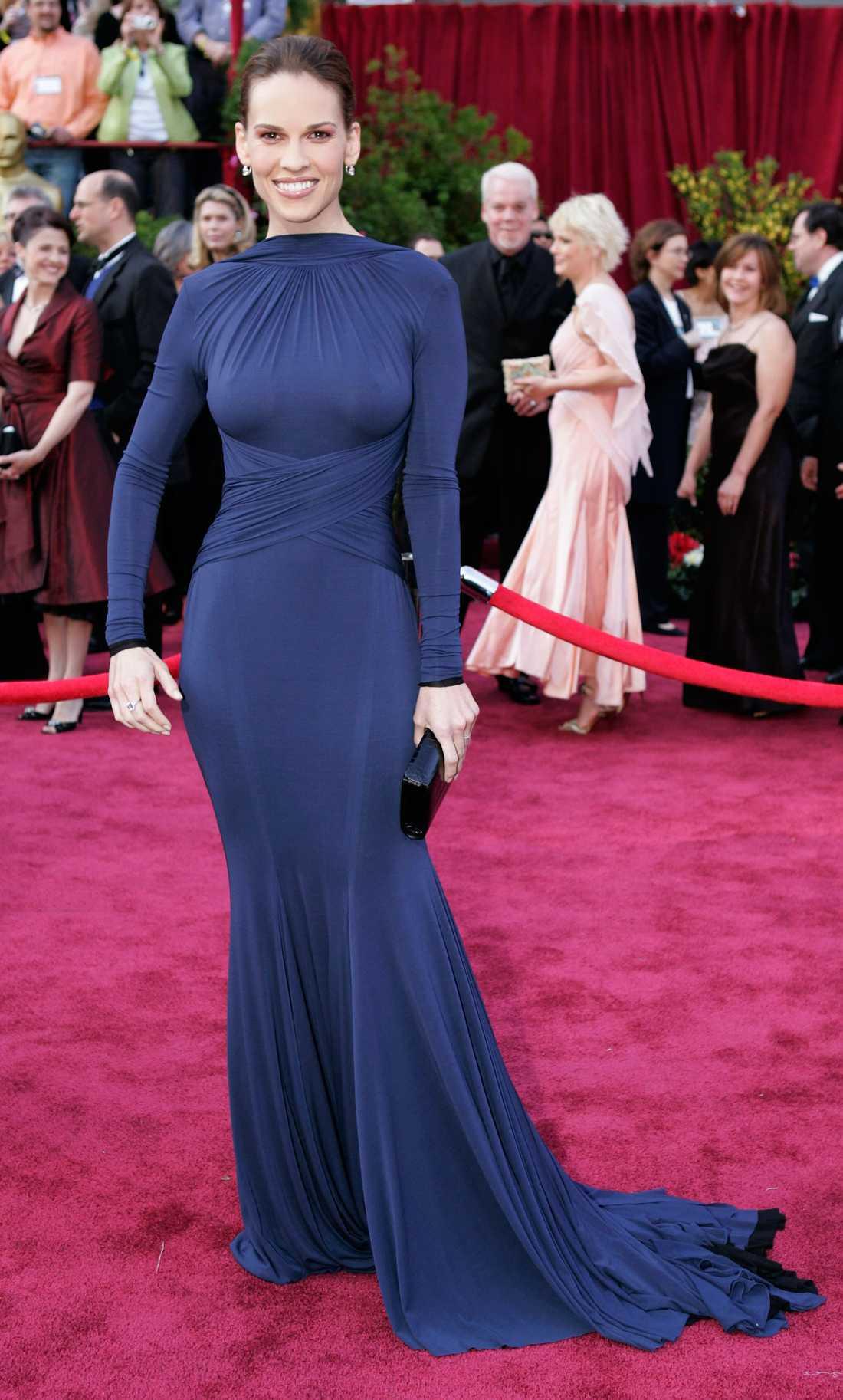 """Hilary Swank 2005 """"I ett snäpp ändrade Swank hur alla kvinnor skulle äntra en röda matta från och med denna kväll. Tidigare hade ingen brytt sig om ryggen. Men från och med nu fick Hollywoods A-listers lära sig hur man poserar snyggt med ryggen mot kameran. Ingen lätt grej. Designern Guy Laroche satte fokus på baksidan och vi har aldrig släppt den sen dess."""""""