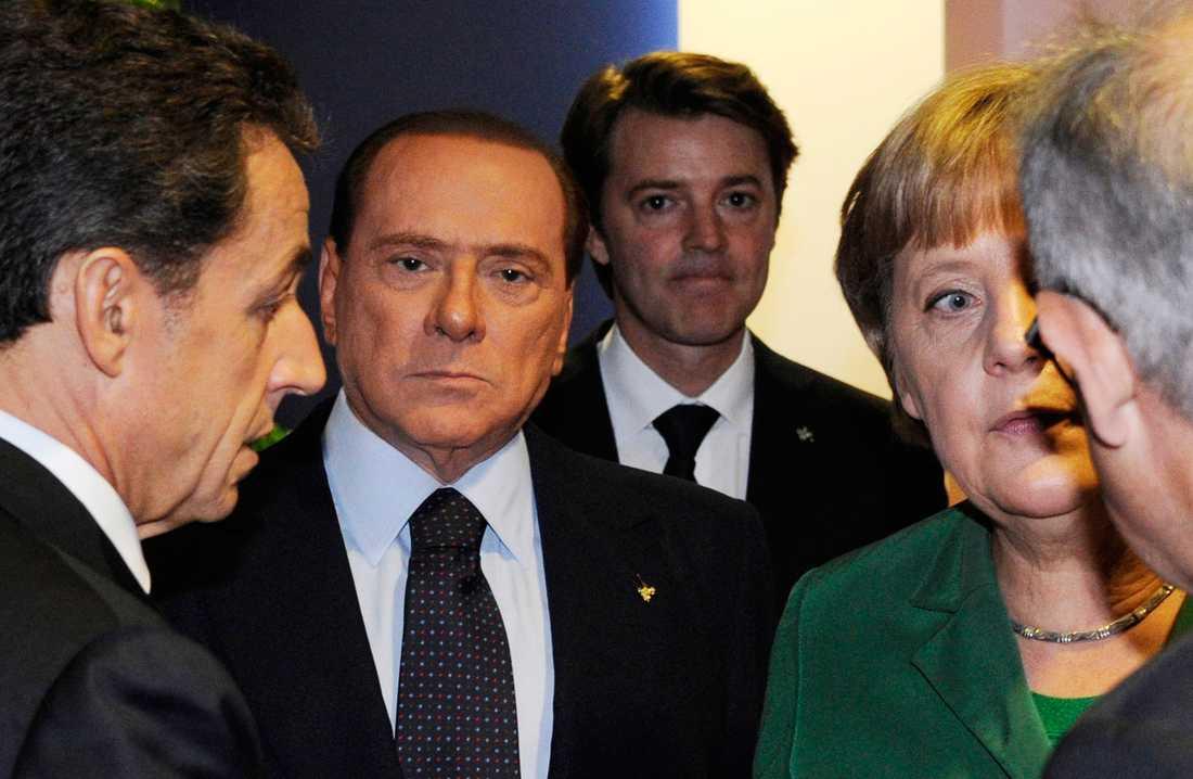 En sammanbiten Silvio Berlusconi mellan Sarkozy och Merkel.