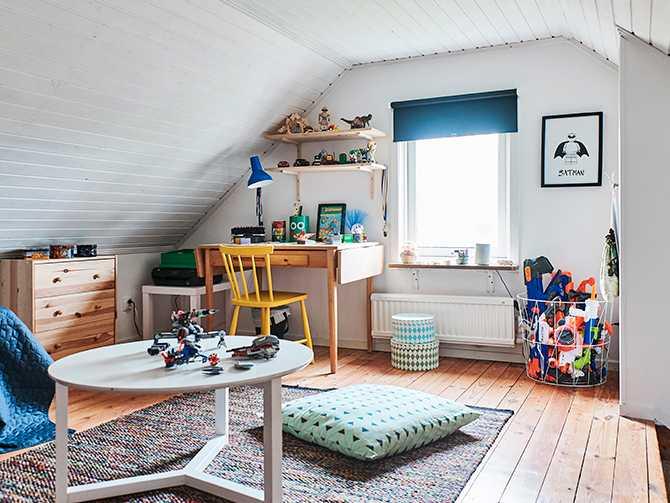 Högst upp i huset, under snedtaket, ligger Jens rum. Den gula stolen är ett ommålat loppisfynd och skrivbordet är egentligen ett bakbord, men funkar lika bra att göra läxorna på. Tavla från Kajsa Visual.