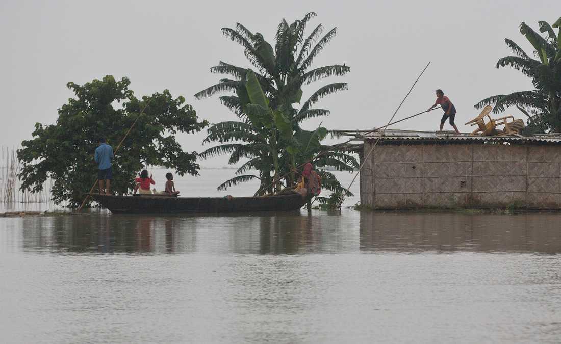 En flicka i Indien som står på ett hustak får hjälp att komma ombord på en båt.