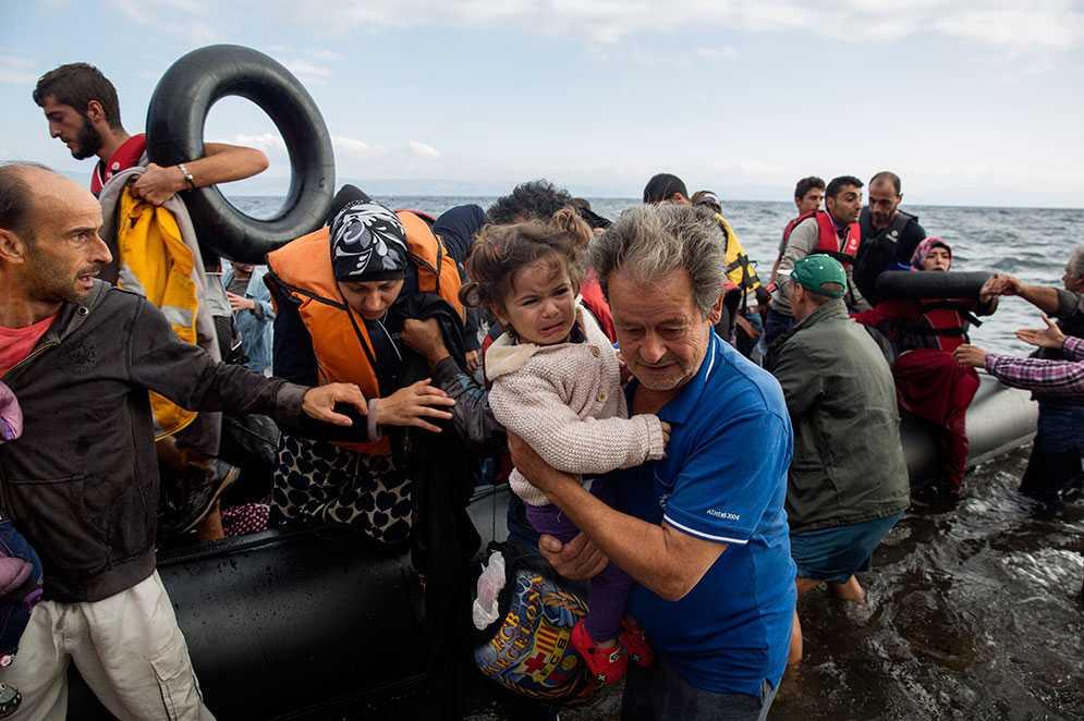 Flyktingar från en ranglig flotte kommer till Lesbos.