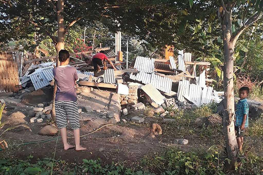 Bild från Nusa Tenggara Barat Disaster Mitigation Agency (BPBD) visar flera personer vid ett förstört hus.