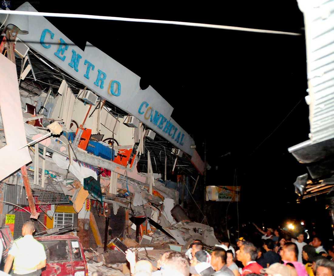 Räddningsarbetare jobbar med att hjälpa överlevande ut ur en kollapsad byggnad i staden Manta.