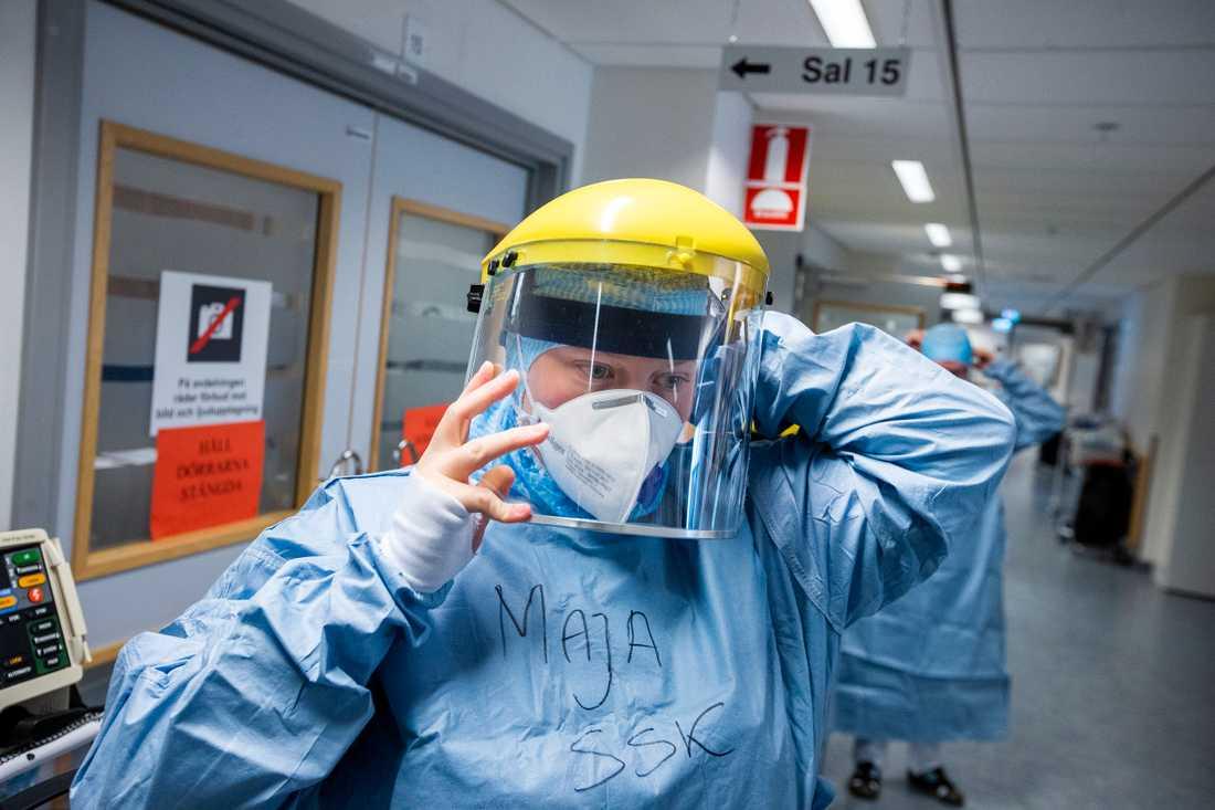 När all skyddsutrustning är på plats trär sjuksköterskan till slut på visiret innan hon går in till patienterna i salen.