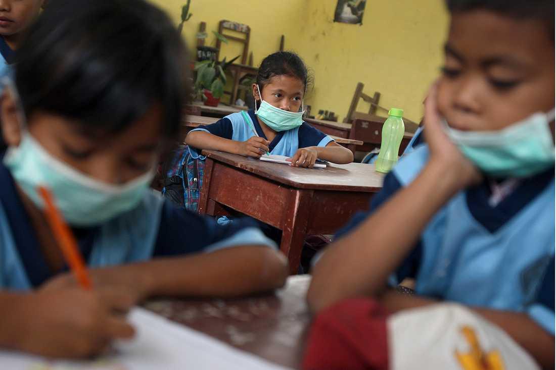 SKYDD MOT VILKANASKA Skolelever med masker för att skydda sig från vulkanaska vid en grundskola i Tiga Nderket, Indonesien. Den 2.600 meter höga vulkanen Mount Sinabung har haft utbrott sedan i söndags.