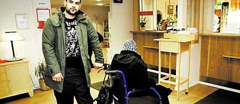"""""""Hur ska de orka?"""" Rinkeby vårdcentral har tvingats säga upp halva personalstyrkan. Mustafa Wali, 21, är assistent åt en rullstolsburen kvinna och på besök ett par gånger i månaden. De är båda bekymrade över framtiden. """"Det märks att de blivit stressade, man är orolig för att de inte ska orka"""", säger han."""