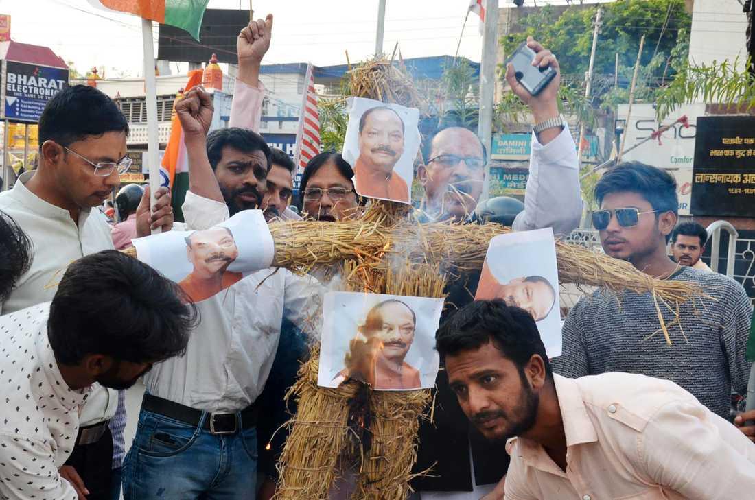 En uppretad folkmassa tänder eld på en docka föreställande delstatsministern Raghubar Dar.