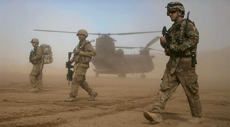 Amerikanska soldater i den Nato-ledda ISAF-styrkan forcerar den virvlande sanden i vinddraget från en Chinook-helikopter i Shindand, väster om Kabul. Foto: AP