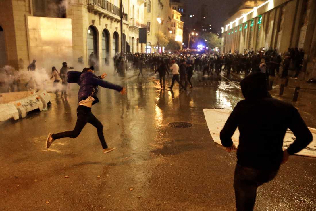 Demonstranter kastar stenar mot kravallpolis under de pågående protesterna i Beirut.