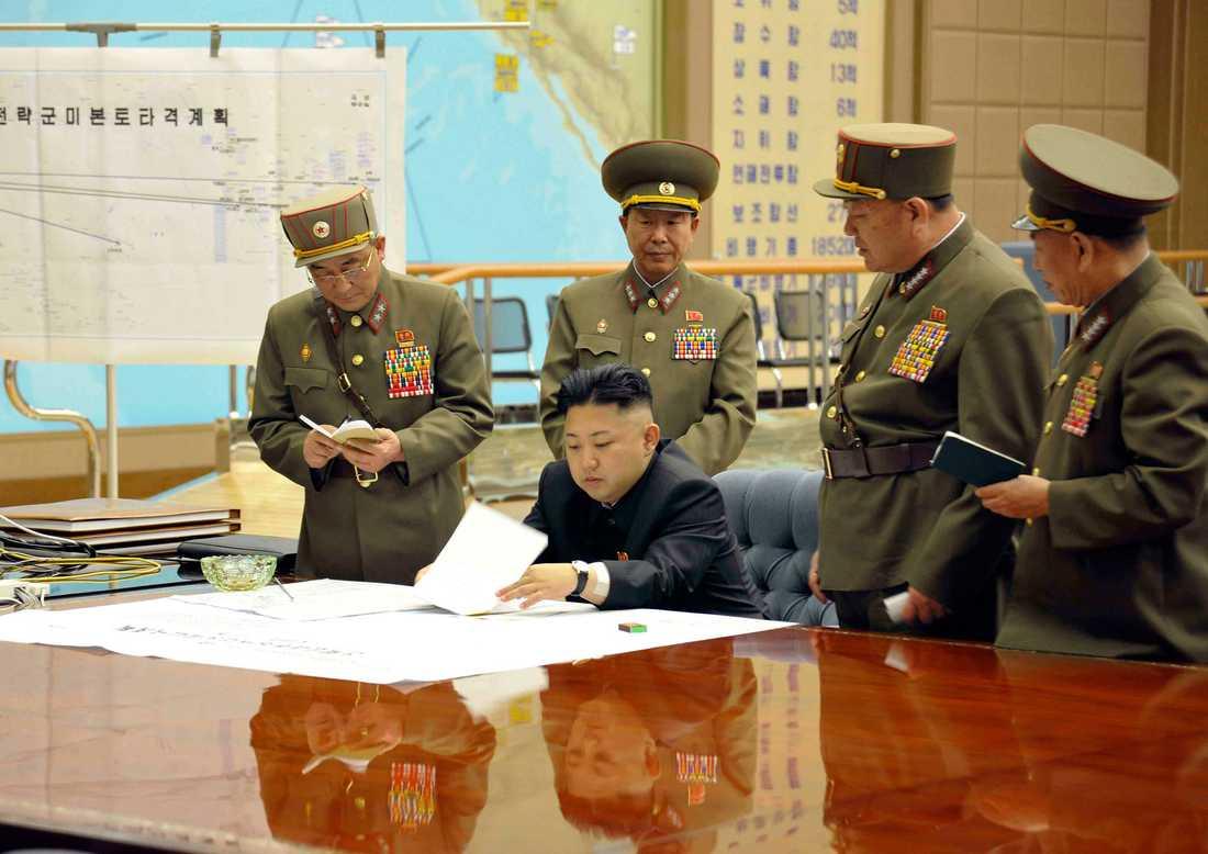 Kim Jong-Un med höga militärer. I bakgrunden syns kartan där flera amerikanska städer är utmärkta som mål.