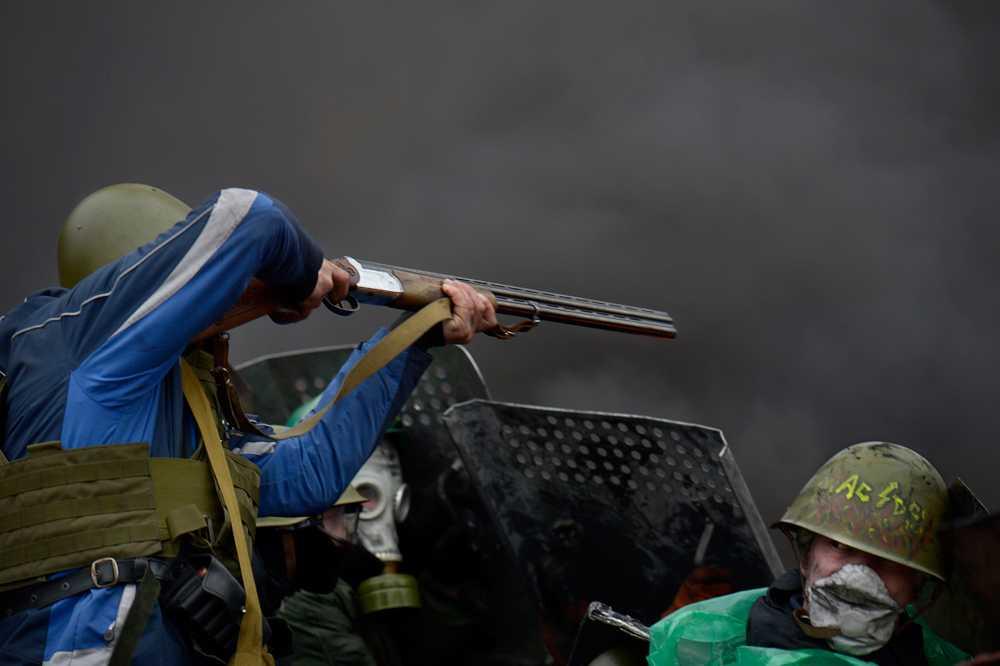 Demonstranter skjuter med hagelgevär mot polisen.