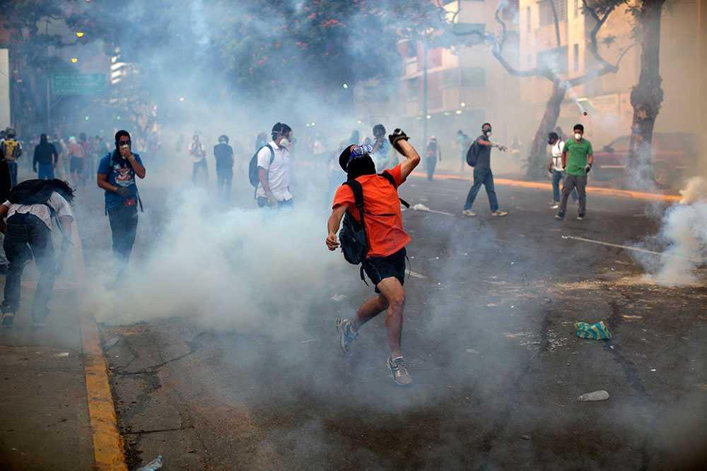 Tårgas Demonstranter i Caracas kastar sten och möts av tårgas från säkerhetsstyrkor.