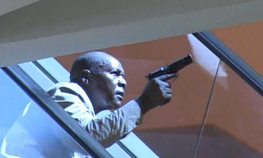 En beväpnad kenyansk polisman tar skydd