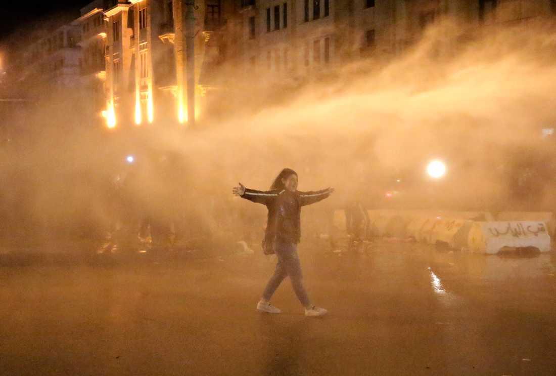 En demonstrant sprejas av vattenkanoner i helgens protester i Beirut.
