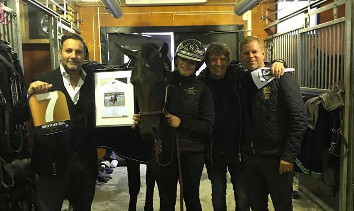 Peter Källberg (håller i nummerbrickan 7) i stallet med hästen.
