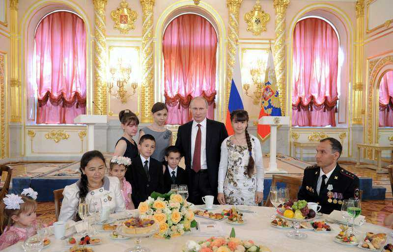 PUTINS FAMILJEDRÖM. Rysslands president Vladimir Putin tillsammans med sjubarnsfamiljen Morokov vid en ceremoni i Kreml där famijer med många barn belönades av staten.