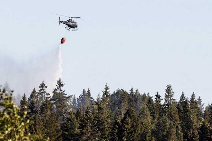 Helikoptrar fortsätter att vattenbomba branden på det före detta skjutfältet.