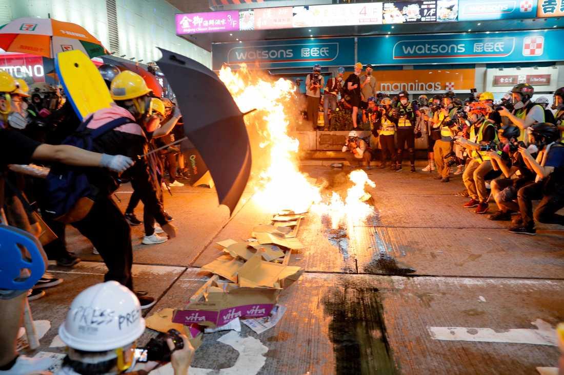 Demonstranter tänder eld på pappkartonger för att hindra polisen att göra framstötningar.
