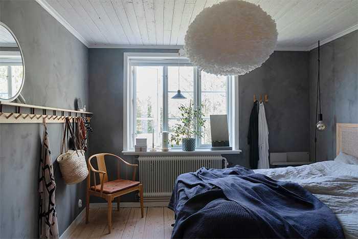 I det stora sovrummet har väggarna målats med grå kalkfärg. Sänggaveln har Debora byggt själv, liksom knopplisten med hyllan som löper längs hela väggen. Fjäderlampan Eos i taket kommer från Umage, och överkast från Himla. Största loppisfyndet är Fritz Hansen-stolen i hörnet som Debora köpt för 150 kronor.