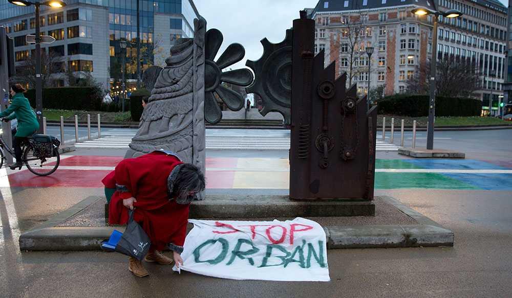 """En kvinna placerar en skylt med budskapet """"Stoppa Orban"""" utanför EU-parlamentet i Bryssel."""
