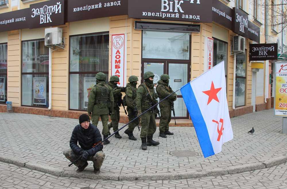Beväpnad män håller i en flagga för den sovjetiska flottan i Simferopol på Krimhalvön.