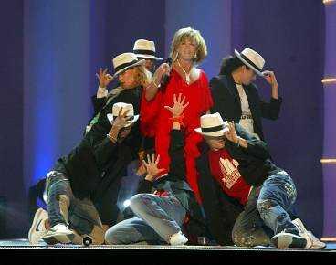 Lill-Babs gör ett hiphopnummer i en raffigt röd klänning omgiven av män på scenen.