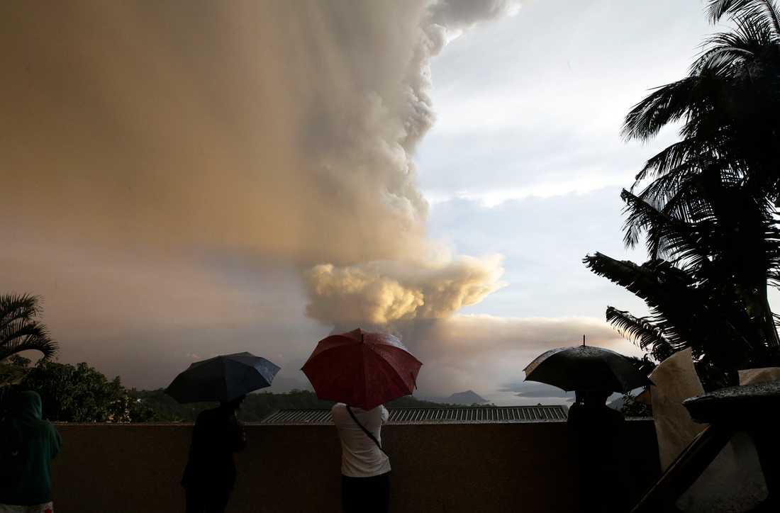 Människor beskådar vulkanen Taal, som sprutar aska utanför Manila.