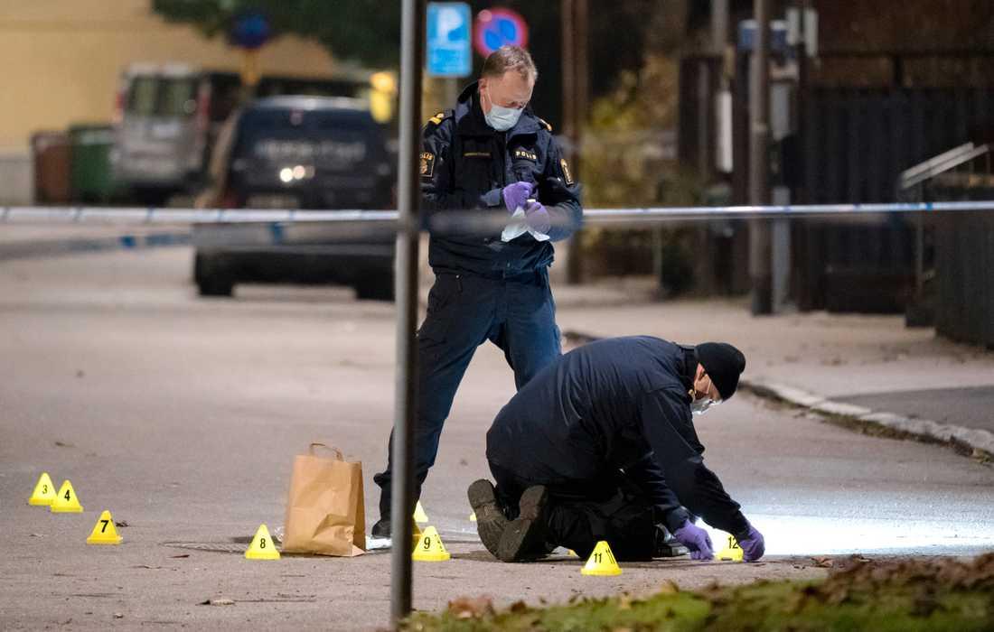 Polisens kriminaltekniker tar hand om en tomhylsa innanför avspärrningarna efter skottlossningen.