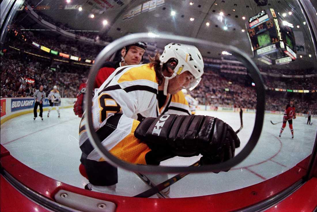 Jagr trycks upp vid sargen mot New Jersey Devils i en slutspelsmatch i maj 1999.