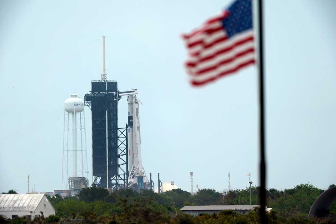 Den startklara Falcon 9-raketen från SpaceX, med besättningskapseln Crew Dragon högst upp, till höger om det svarta tornet på Kennedy Space Center.