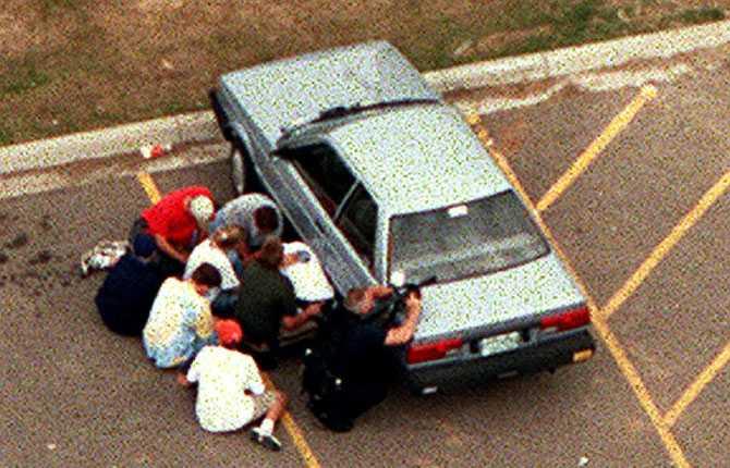 Elever i skydd bakom en bil och i sällskap av beväpnad polis. Bara ett par meter från dem har en av deras skolkamrater just skjutits ihjäl.