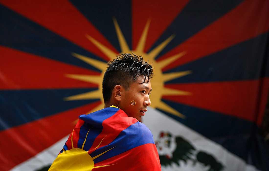 FÖR ETT FRITT TIBET En tibetan i New Delhi, Indien bär en tibetansk flagga under ett protestmöte. Demonstranterna kräver frisläppandet av tibetanska politiska fångar i Kina.