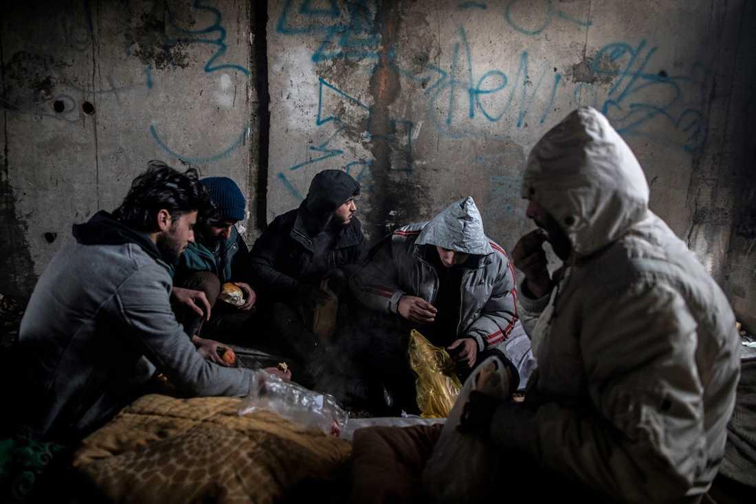 En grupp syrier äter frukost i en övergiven byggnad utanför Bihac i Bosnien-Hercegovina. Många migranter och flyktingar söker sig genom Bosnien för att ta sig in i EU via Kroatien. Arkivbild.