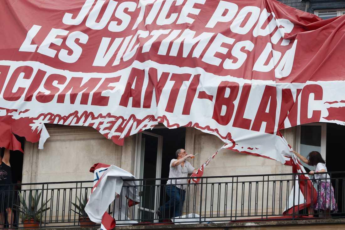 Boende river sönder en främlingsfientlig banderoll i Paris.