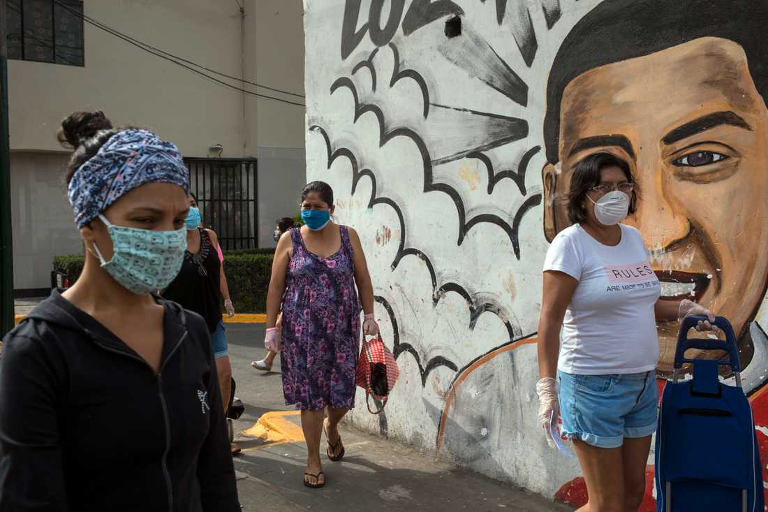 Kvinnor i skyddsmasker köar för att köpa mat på en marknad i Perus huvudstad Lima i lördags.