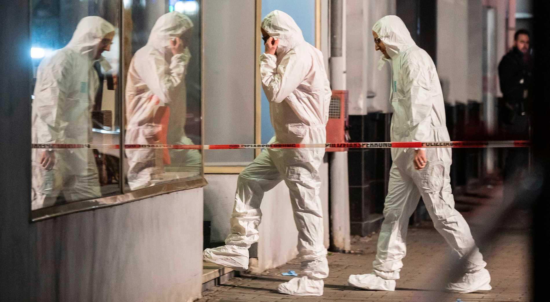 Polisens tekniker går in i byggnaden efter onsdagens skjutningar