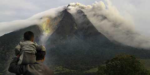 En pappa och hans son ser vulkanen Mount Sinabung spy ut sin tjocka rök, i bland upp till 1500 meter upp i luften och sen ut över Karo-distriktet på norra Sumatra. Tusentals boende tvingas nu fly sina hem undan faran.