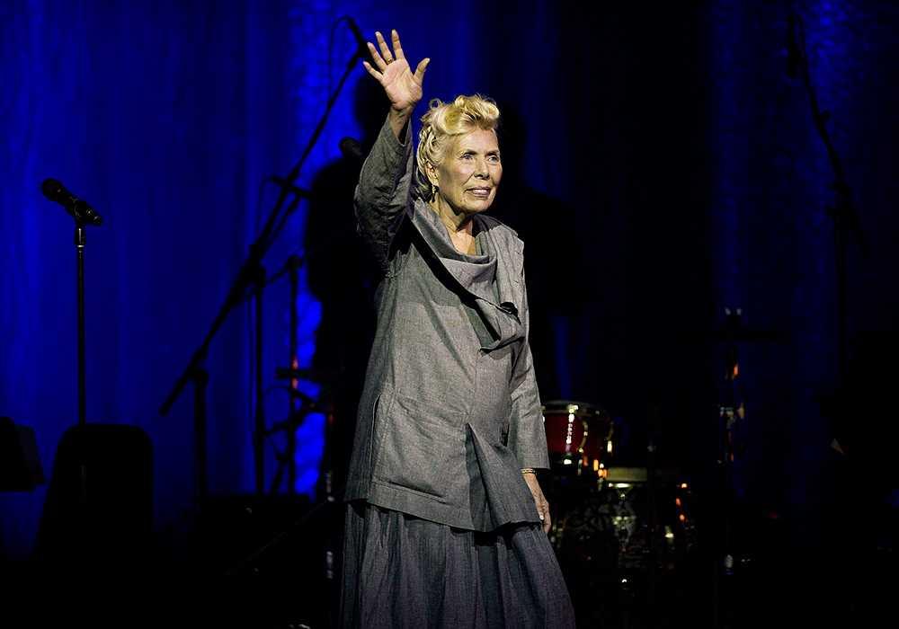 Joni Mitchell vinkar till publiken under jubileumskonserten när sångerskan fyllde 70.