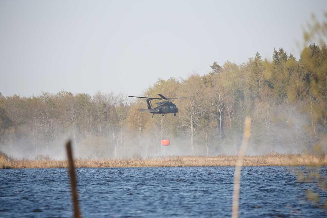 En helikopter hämtar vatten i sjö för att vattenbomba i Hästveda.
