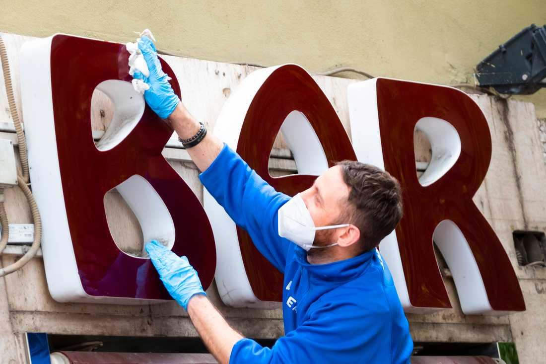 En man torkar skylten utanför en bar i Italiens huvudstad Rom inför måndagens lättnader i coronarestriktionerna.