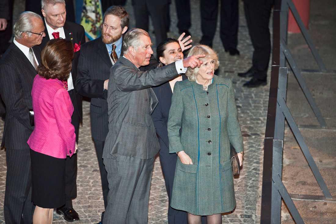 Prins Charles tittar och pekar.