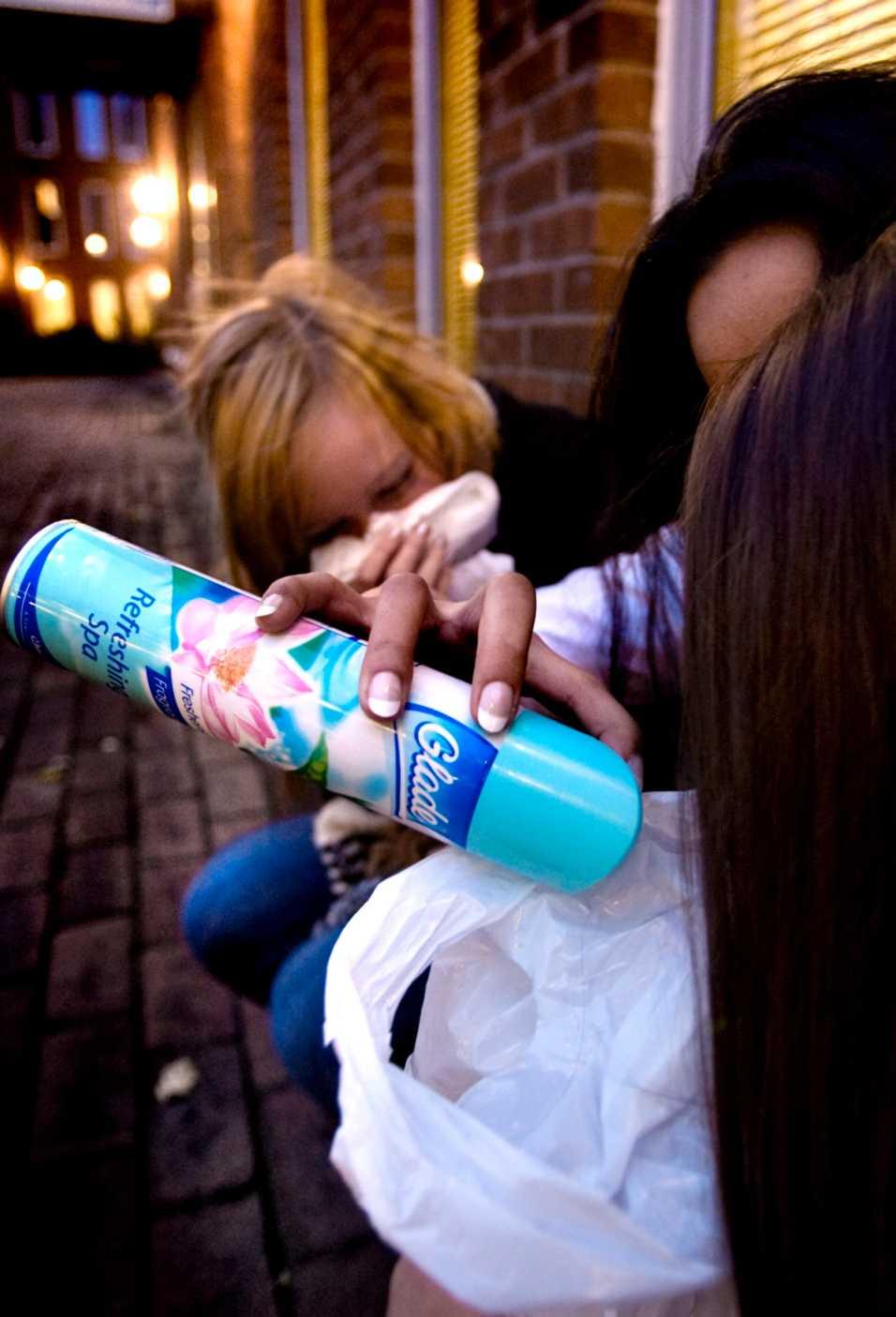 Flickorna sprayar gasen i en påse för att kunna sniffa den. Nu varnar socialsekreterare för riskerna. OBS! Bilden är arrangerad.