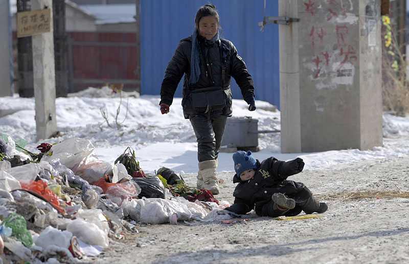 Ett litet barn tappat balansen i det hala väglaget i Peking i Kina. En köldknäpp håller Kina i ett hårt grepp.