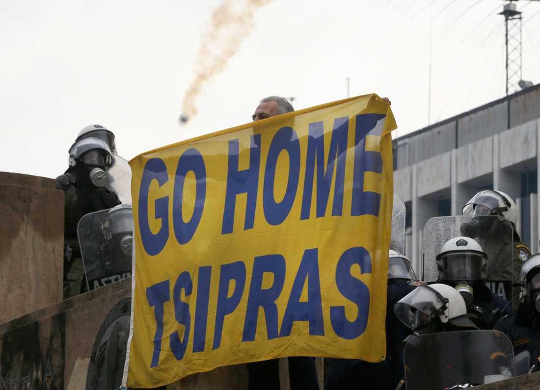 En demonstrant håller upp en banderoll i protest mot Greklands premiärminister Alexis Tsipras under den stora demonstrationen mot Makedoniens namnbyte i Aten i söndags.