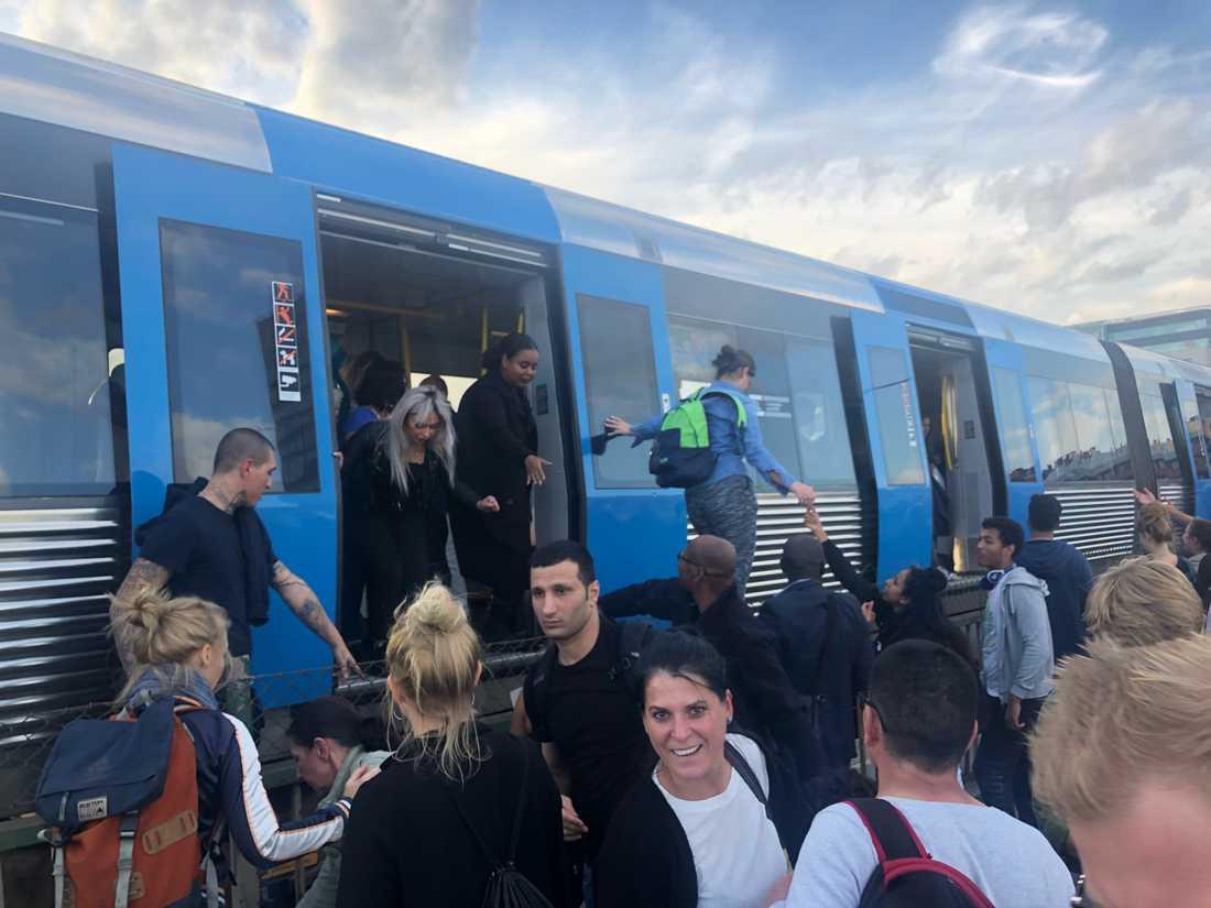 Resenärer evakueras från stillastående tåg.