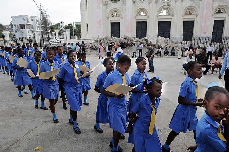 Elever sjunger vid en mässa vid den rasade katedralen i Port-au-Prince.